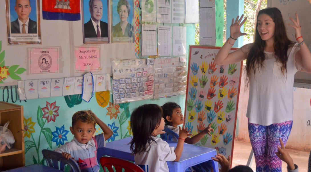Joven voluntaria en Camboya le enseña a los niños frases en inglés.